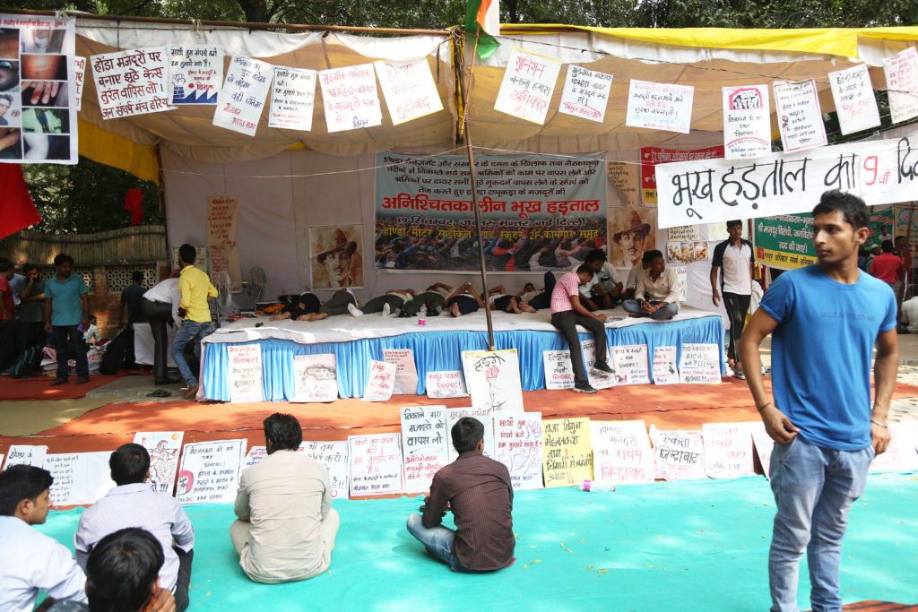 Honda workers on their ninth day of fast take rest while laying down on the stage at Jantar Mantar. Credit: Hina Fathima