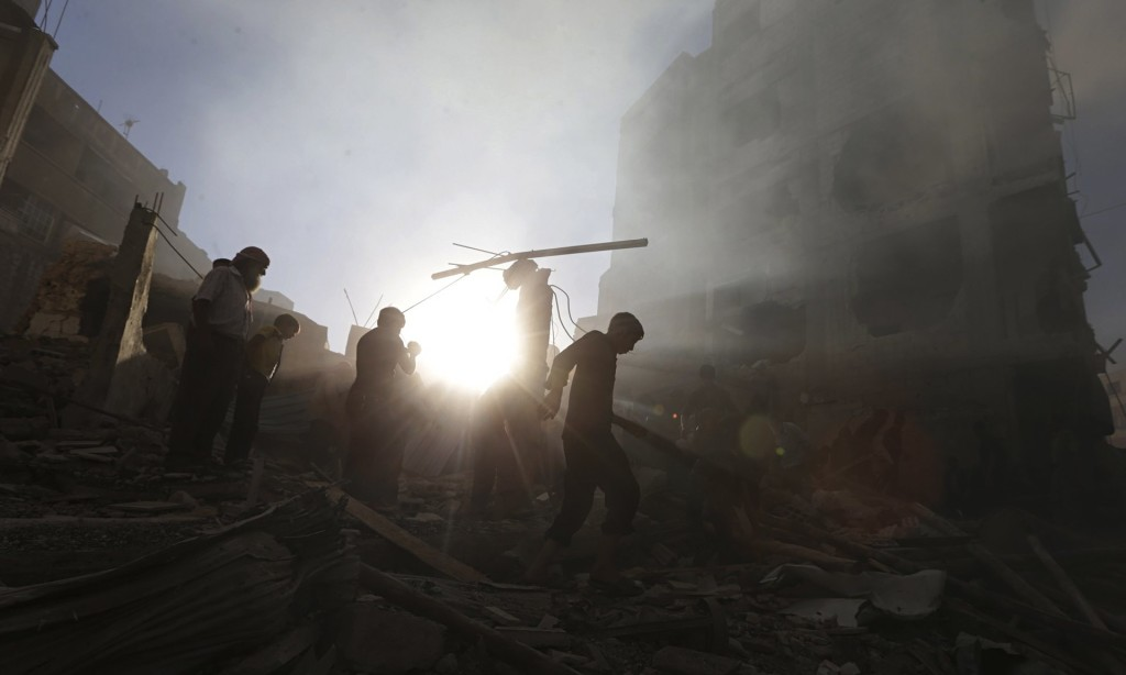 Residents of a Damascus suburb pick up the pieces after an airstrike. Credit: Reuters/Bassam Khabieh