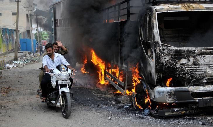 Men ride a motorcycle past a lorry in Bengaluru, which was set on fire by protesters after the Supreme Court ordered Karnataka to release 12,000 cubic feet of water per second every day from the Cauvery river. Credit: Reuters