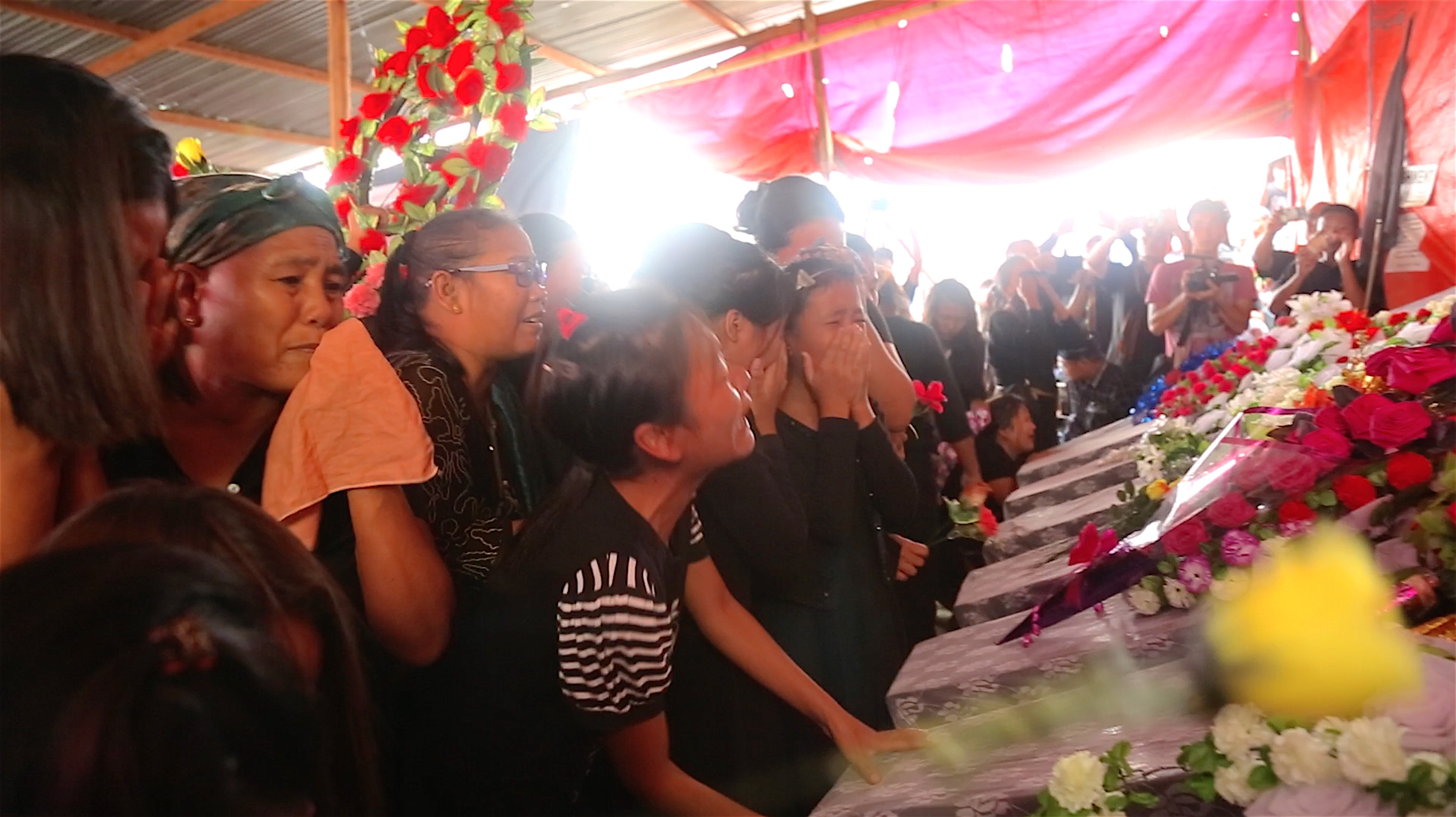 Women and children pay respect to the dead with flower tribute on the symbolic coffins. Credit: Akhil Kumar
