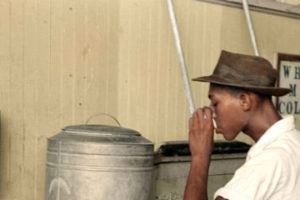 "A black man drinking at 'Coloured' water cooler in streetcar terminal, Oklahoma City, Oklahoma"" circa July 1939. Credit: Jared Enos/Flickr, CC BY-NC-ND 2.0"
