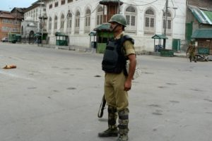 A security Jawan stands guard during curfew in Srinagar. Credit: PTI