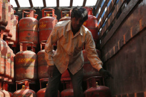 A worker unloads liquefied petroleum gas (LPG) cooking cylinders from a supply truck outside a distribution centre in the western Indian city of Ahmedabad February 19, 2015. India may slash its food and fuel subsidy bill by about $8 billion in next week's budget, two sources said, but despite the impressive headline, the cut is not as radical as free market champions had hoped for in Prime Minister Narendra Modi's first full budget.   REUTERS/Amit Dave (INDIA - Tags: BUSINESS ENERGY POLITICS) - RTR4QDPH