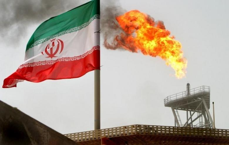 A gas flare on an oil production platform is seen alongside an Iranian flag in the Gulf July 25, 2005. Credit: Reuters/Raheb Homavandi/File Photo