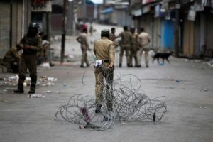 A policeman pulls concertina wire to lay a barricade on a road during a curfew in Srinagar July 12, 2016. Credit: Danish Ismail/Reuters