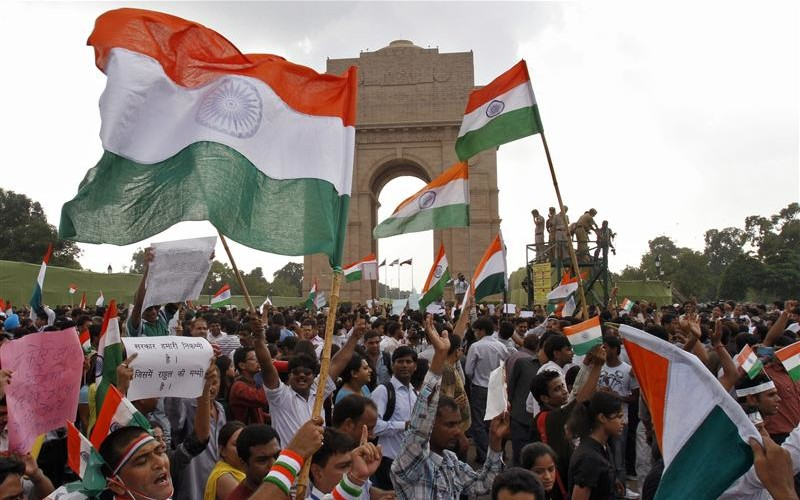 Supporters of veteran Indian social activist Anna Hazare raise Indian national flags during a protest march against corruption in front of India Gate in New Delhi August 17, 2011. Protests swelled across India on Wednesday in support of a self-styled Gandhian anti-corruption campaigner fasting to the death in jail, with Prime Minister Manmohan's Singh's beleaguered government apparently unable to end the standoff. Credit: Reuters
