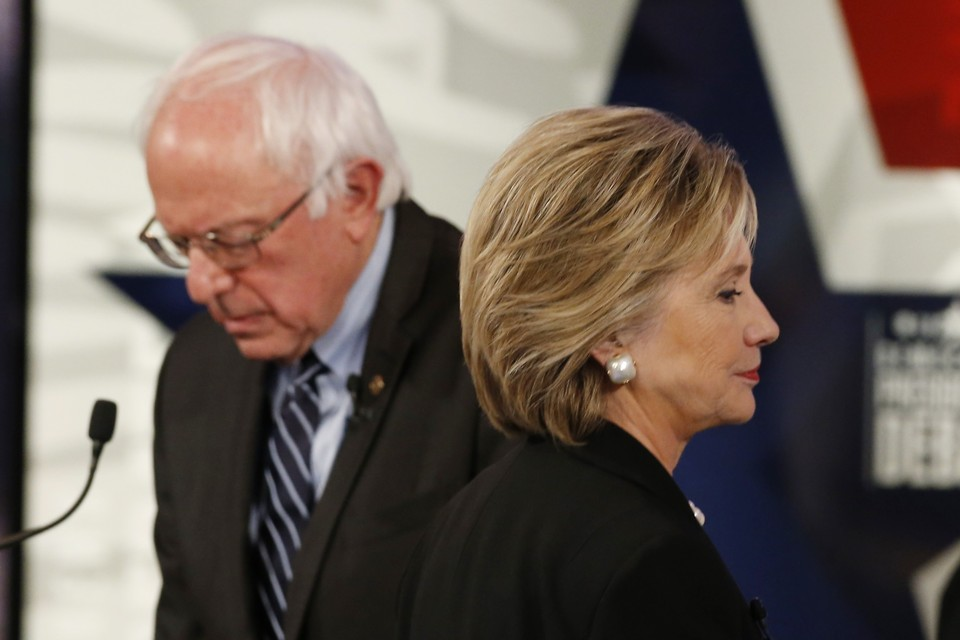 Democratic U.S. presidential candidate former Secretary of State Hillary Clinton walks past fellow candidate and Senator Bernie Sanders during a break at the second official 2016 U.S. Democratic presidential candidates debate in Des Moines, Iowa, November 14, 2015. REUTERS/Jim Young - RTS73OZ