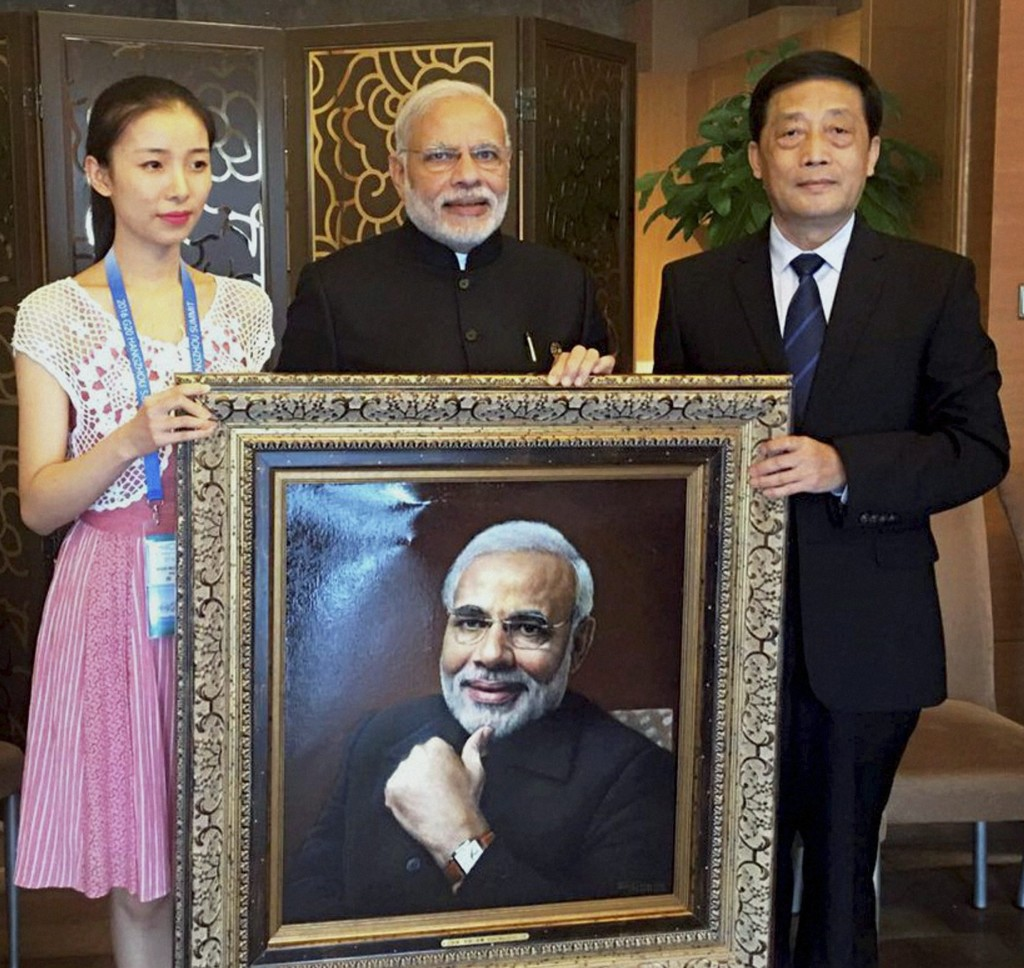 "Prime Minister Narendra Modi is presented with his portrait by painter Shen Shu of the Hangzhou's Zhejiang Kaiming Art Gallery on Sunday. ""Thank you to painter Shen Shu & his team from Hangzhou''s Zhejiang Kaiming Art Gallery for the special gesture"", Modi tweeted later. Credit: PTI"