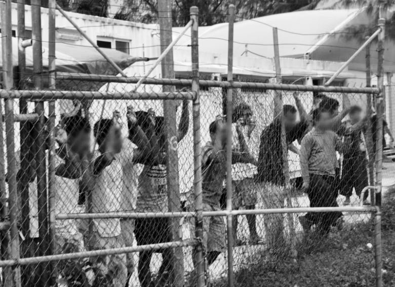 Asylum-seekers look through a fence at the Manus Island detention centre in Papua New Guinea. Eoin Blackwell/AAP/via Reuters