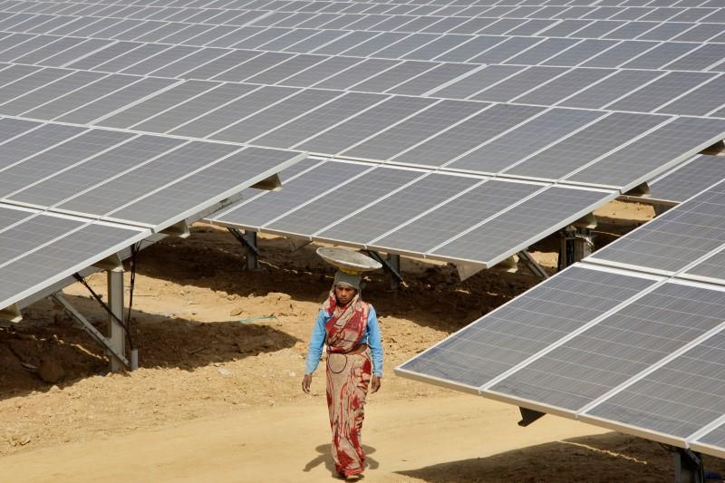A worker walks through the installed solar modules at the Naini solar power plant in Allahabad. Credit: Reuters/Jitendra Prakash/Files