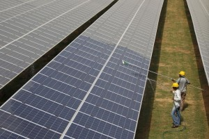 Workers clean photovoltaic panels inside a solar power plant in Gujarat. Credit: Reuters/Amit Dave/Files