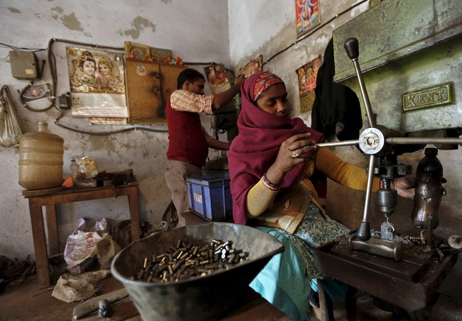 A worker makes auto parts on a machine inside a workshop in Faridabad, India, on December 24, 2015. Credit: Reuters