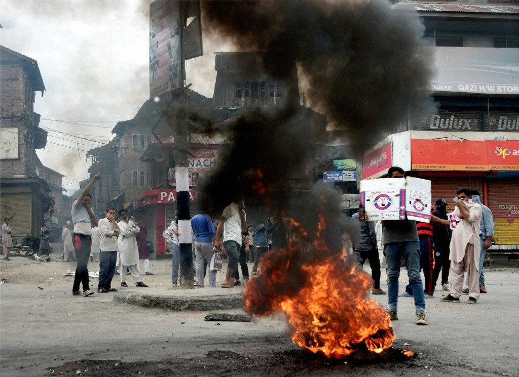 Protesters block a road by burning tyres during a strike after curfew was completely lifted, in Srinagar on Wednesday. Credit: PTI/S. Irfan