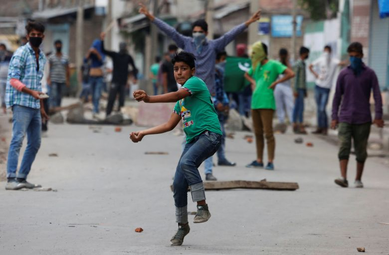 A protester throws stones towards the Indian police during a protest in Srinagar against the recent killings in Kashmir, August 9, 2016. Credit: Reuters