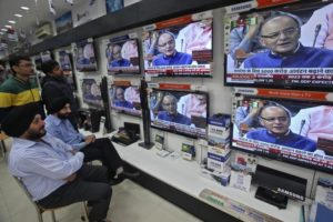 People watch television sets displaying India's Finance Minister Arun Jaitley presenting the budget in parliament, at an electronic shop in the northern Indian city of Chandigarh February 28, 2015. Jaitley on Saturday announced a budget aimed at high growth, saying the pace of cutting the fiscal deficit would slow as he seeks to boost investment and ensure that ordinary people benefit. REUTERS/Ajay Verma (INDIA - Tags: BUSINESS) - RTR4RIGO
