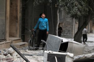 A youth inspects a damaged site after an airstrike in the besieged rebel-held al-Qaterji neighbourhood of Aleppo, Syria October 14, 2016. Credit: Reuters