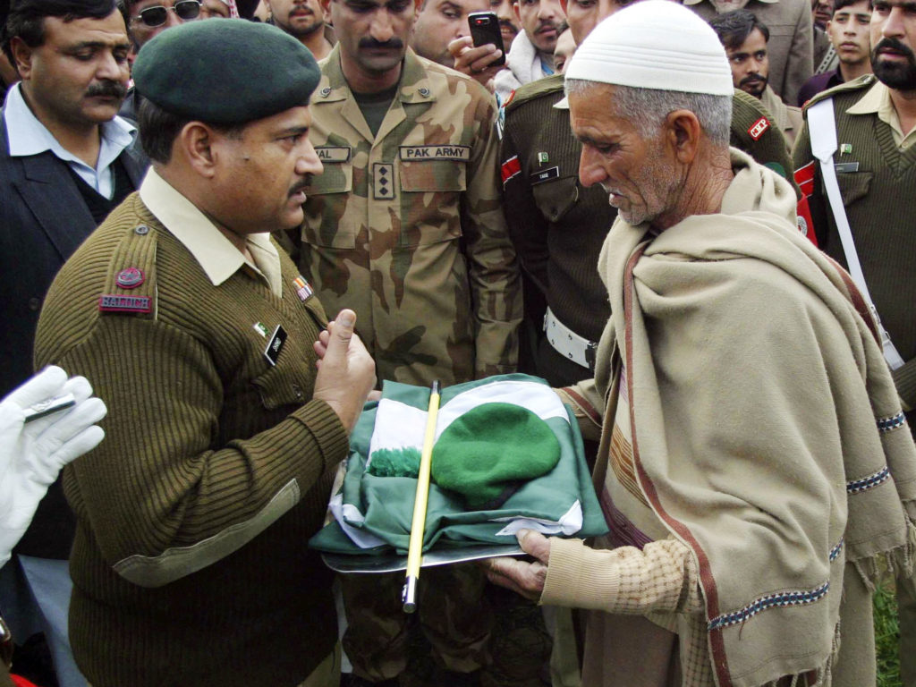 A military official hands over a Pakistan military cap, stick and national flag to the father of Pakistani soldier Muhammad Akhlaq, whom the Pakistan military said was killed by Indian soldiers while crossing into the Indian side of Kashmir. Credit: Reuters