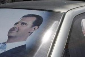 Election poster of Syria's President Bashar al-Assad and a photo of Russian President Vladimir Putin (R) are seen on a car at al-Qardahah town near Latakia city May 26, 2014. Credit: Reuters