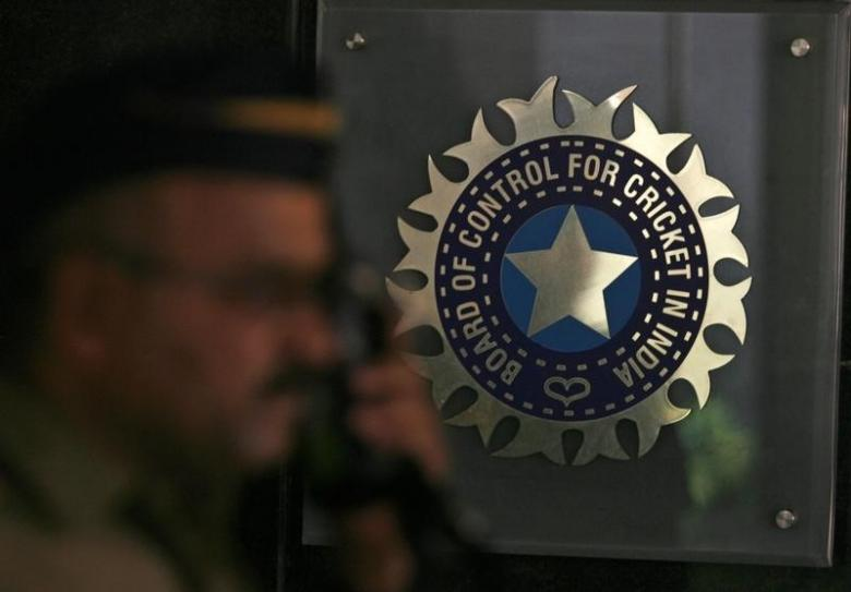 A policeman walks past a logo of the Board of Control for Cricket in India (BCCI). Credit: Reuters