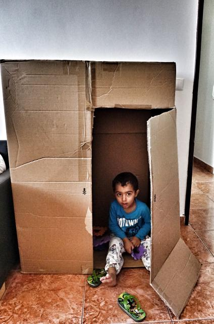 Lokman playing hide and seek in a fridge carton. While playing, he acts out he family's escape from Aleppo, though he was to young to understand. Credit: Shome Basu