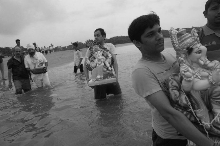 Mumbaikers carrying Ganesha idols for immersion in the Arabian Sea. The idols are made from plaster of Paris and poisonous dyes that lead to pollution, thereby negatively impacting the environment.