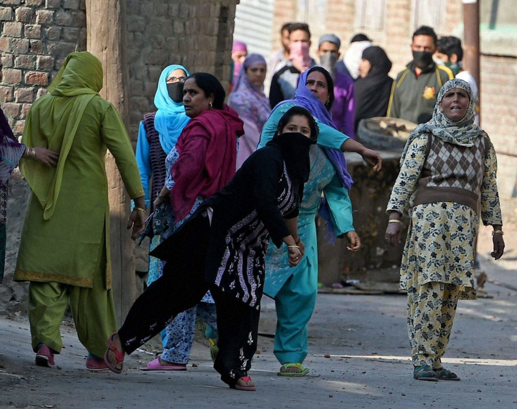Protesters throw stones at policemen during a protest in Srinagar. Credit: PTI
