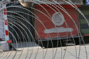 A policeman stands guard next to concertina wire laid across a road during a curfew in downtown Srinagar. Credit: Reuters/Danish Ismail