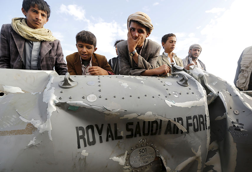 People stand by part of a Saudi fighter jet found in Bani Harith district north of Yemen's capital Sanaa, May 24, 2015. Credit: Reuters/Khaled Abdullah