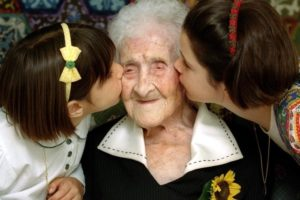 The World's oldest woman, Jeanne Calment, 120 years old, is kissed by two young girls during a special ceremony in a retirement home in Arles, Southern France, February 21, 1995. Credit: Reuters/Jean-Paul Pelisser/File Photo