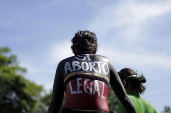 """In this 2012 file photo, a woman sits in a float with """"Yes abortion legal"""" written on her back during a protest in San Salvador. Credit:Reuters/Ulises Rodriguez"""