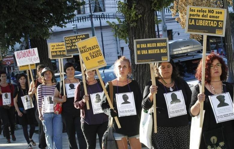 Members of feminist organisations hold signs during a rally against gender violence . Credit: Reuters/Rodrigo Garrido