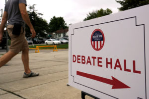 A man walks past a sign for the US vice-presidential debate at Longwood University in Farmville, Virginia October 2, 2016. Credit: Reuters/Rick Wilking