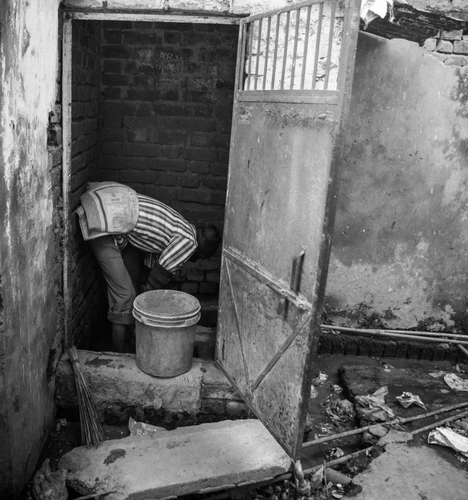 A man cleaning a dry latrine. Credit: Sharada Prasad CS/Flickr CC BY 2.0