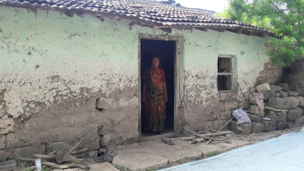 The hut where Prabhatbhai lived with his family of eight, his wife standing at the door. The picture was clicked when he was still being treated. Credit: Damayantee Dhar