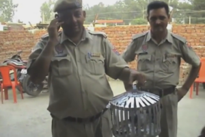 Policemen in Pathankot with  the pigeon that has been detained on suspicion of terrorist links.  Credit:  Screen grab from rt.com