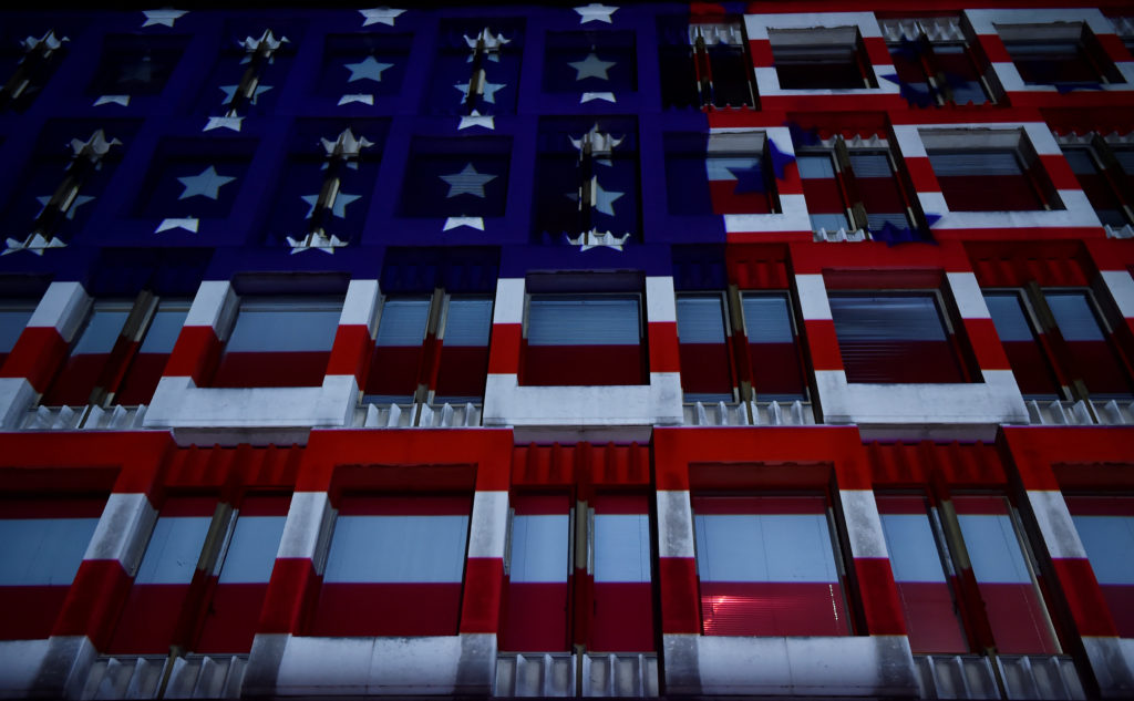 A U.S. flag is projected on the facade of the U.S. Embassy, during the U.S. Presidential election, in London, Britain, November 8, 2016. REUTERS/Hannah McKay