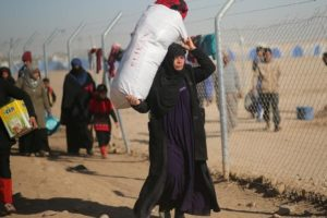 A displaced Iraqi woman, who fled the Islamic State stronghold of Mosul, carries her belongings at Khazer camp, Iraq November 26, 2016. Picture taken November 26, 2016.  REUTERS/Mohammed Salem