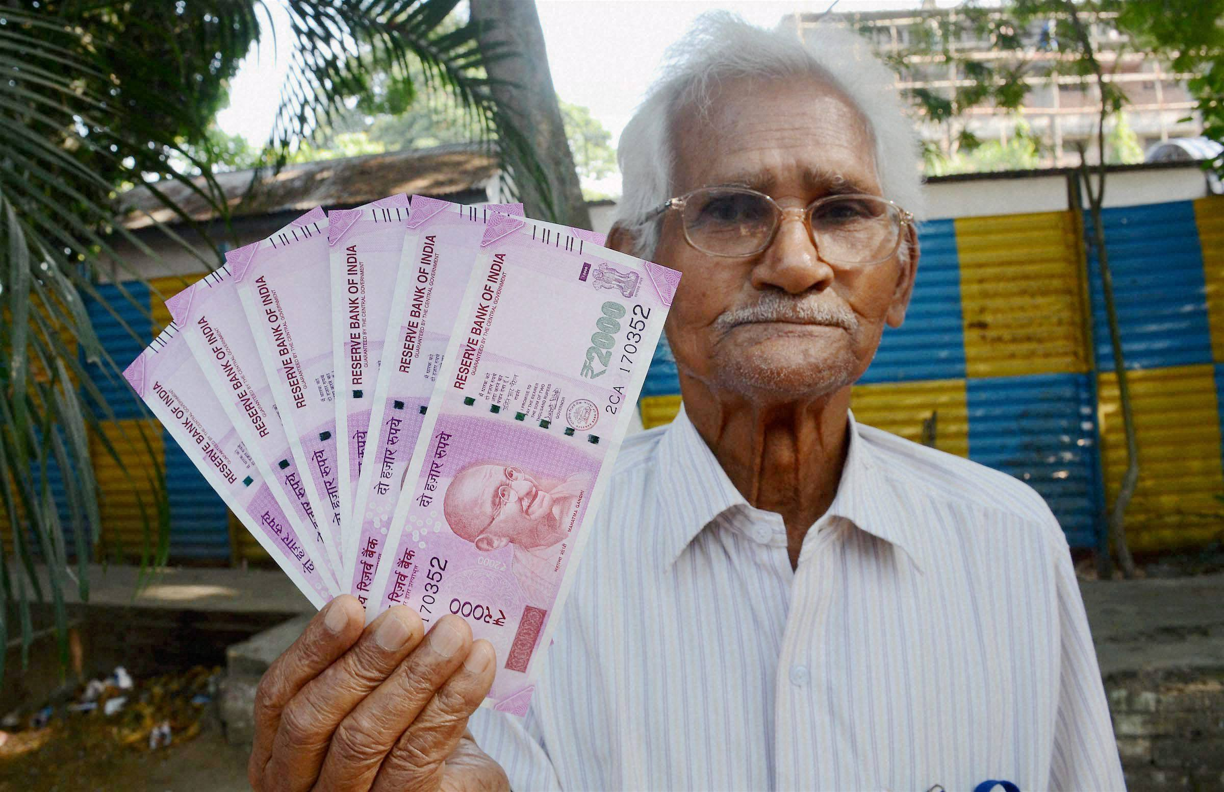 A senior citizen showing Rs 2,000 notes after exchanging old notes in Guwahati. Credit: PTI