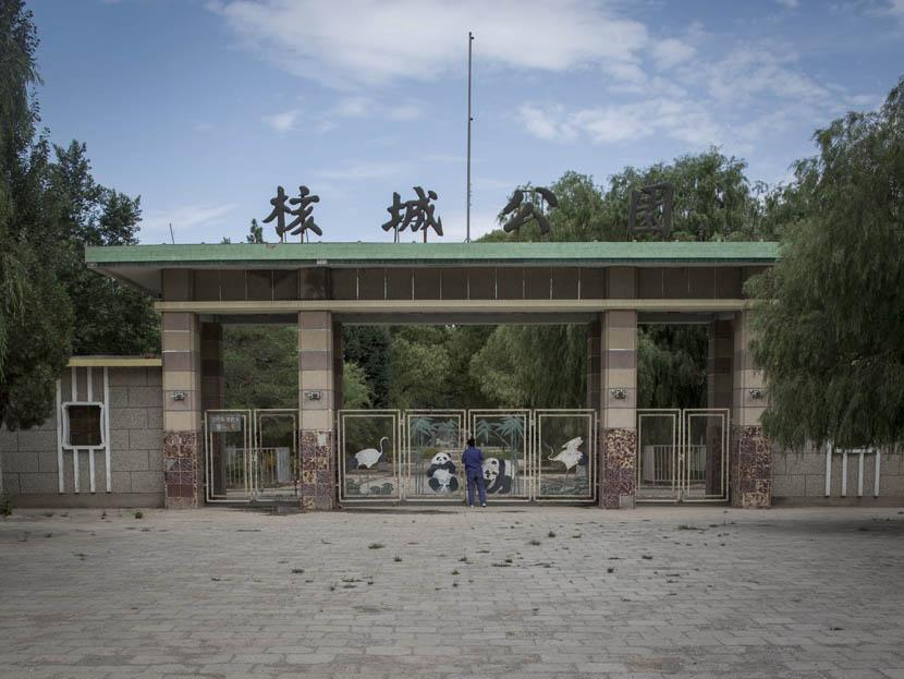 A woman peers through the gate at the Nuclear City Park in 404 City. Credit: Xu Haifeng/Sixth Tone