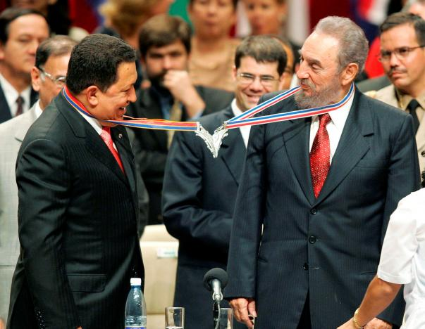 Venezuela's President Hugo Chavez (L) and his Cuban counterpart Fidel Castro joke after joining their medallions, given by medical graduates, at Havana's Karl Marx theatre, in this August 20, 2005 file photo. Credit: Reuters/Claudia Daut/File Photo