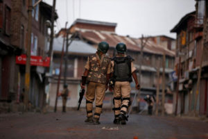 Policemen patrol a deserted road during a curfew in Srinagar. Credit: Reuters
