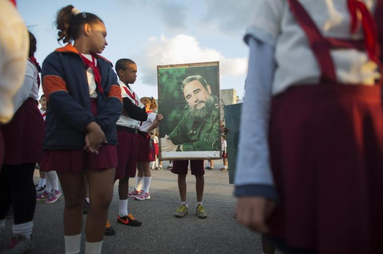 A student holds a photograph of Cuba's former President Fidel Castro near the memorial of Jose Marti on Revolution Square in Havana January 28, 2015. Credit:Reuters/Alexandre Meneghini
