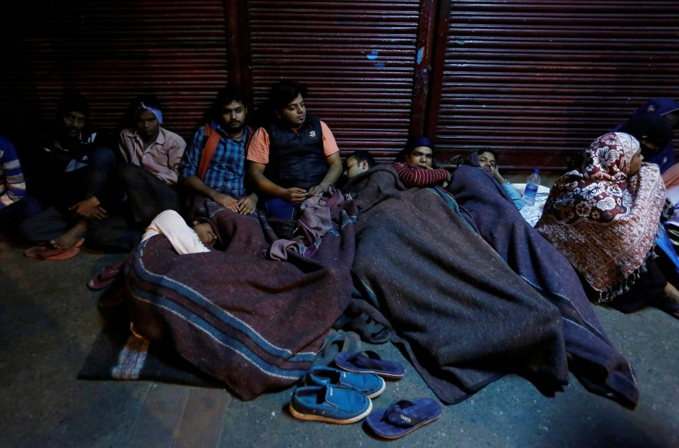 People sleep outside a bank as they wait for the bank to open to exchange their old high denomination bank notes in the early hours, in the old quarters of Delhi, November 16, 2016. Credit: Reuters/Adnan Abidi