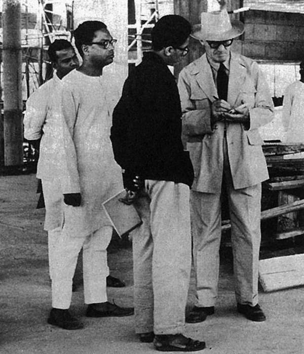 A young Doshi in a black jacket on a construction site with Le Corbusier.