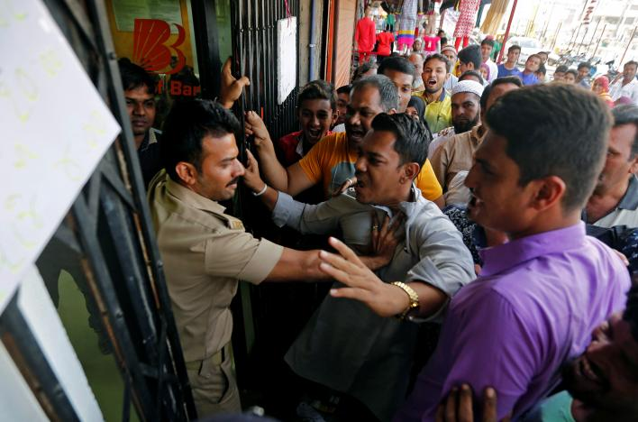 People scuffle with a policeman as they try to enter a bank to exchange their old high denomination banknotes in Ahmedabad, India, November 17, 2016. Credit: Amit Dave/Reuters