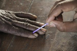 A voting official marks the finger of a voter inside a polling booth during the second phase of state elections, in Azamgarh town in the northern Indian state of Uttar Pradesh February 11, 2012. Credit: Reuters/Files