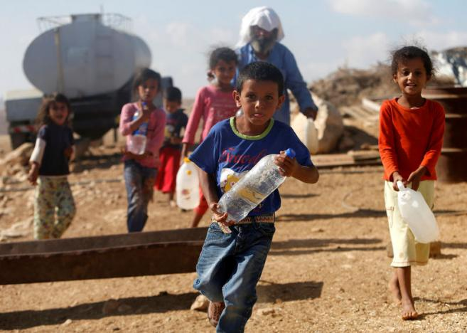 Palestinian children carry water bottles near their house on the outskirts of the West Bank village of Yatta, south of Hebron, August 17, 2016. Credit: REUTERS/Mussa Qawasma