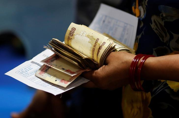 A woman holds 500 and 1000 Indian rupee banknotes as she stands in a queue to deposit her money inside a bank in the northern city of Kanpur, India, November 10, 2016. Credit: Adnan Abidi/Reuters/Files