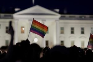A rainbow flag is held up during a vigil after the worst mass shooting in U.S. history at a gay nightclub in Orlando, Florida, in front of the White House in Washington, U.S., June 12, 2016. REUTERS/Joshua Roberts