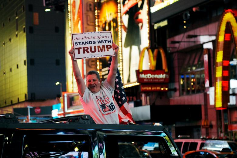 A man leans out of a Hummer shouting words in support of Donald Trump while driving through Times Square in New York. REUTERS/Mark Kauzlarich